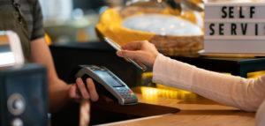Neue Normalität im Einzelhandel: Kunde, der dank kontaktloser Zahlung mit einem Mobiltelefon bezahlt.