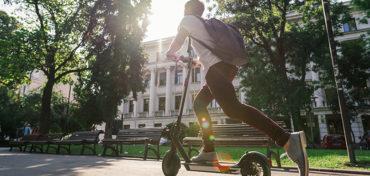 Mobilität in einer intelligenten Stadt: ein Mann fährt auf einem E-Roller durch den Park