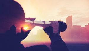 Man looking through binoculars at cityscape