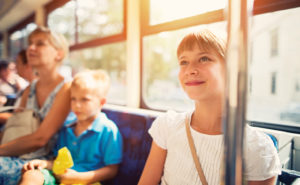 Happy kids travelling on a bus with their mother