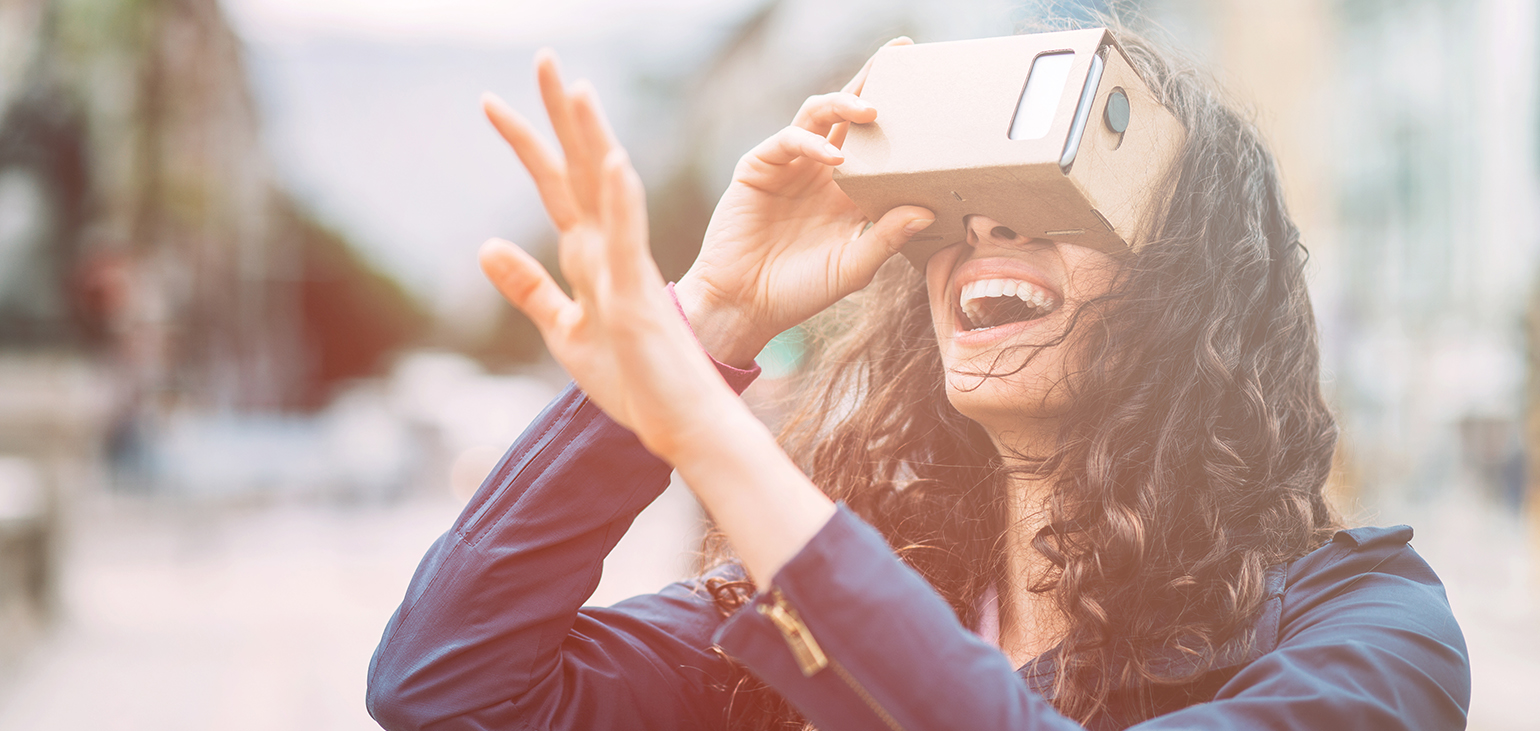 Young woman holding a cardboard virtual reality simulatop and gesturing