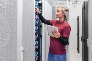 Staff working in server room. Aware or unaware of a potential cyber attack. Survey shows only 15 % of companies are adequately  prepared for a cyber attack
