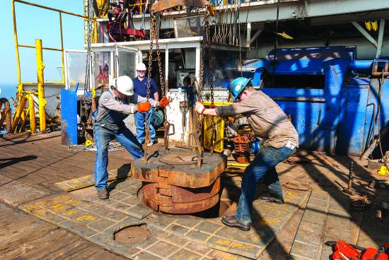 Oil rig workers drilling a whole