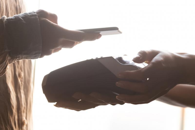 Zoomed view of a payment, one customer holding her phone above card machine