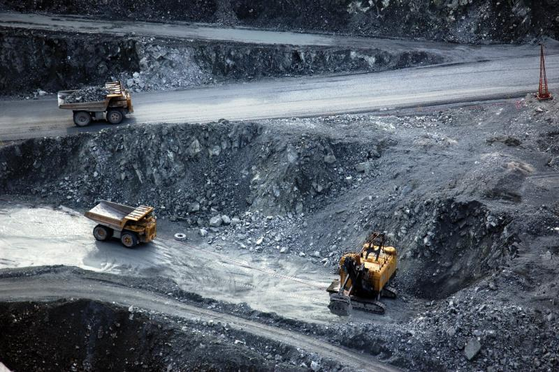Dump trucks work in a open pit mining