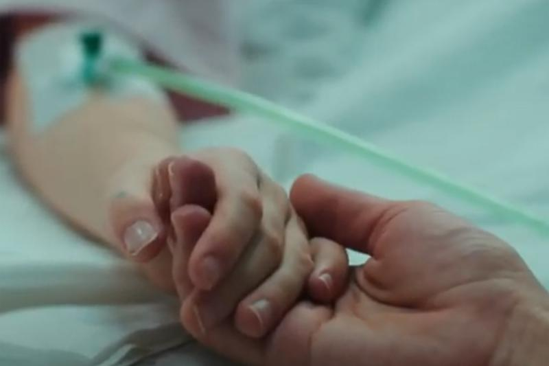 close up of a patient and relative holding hand