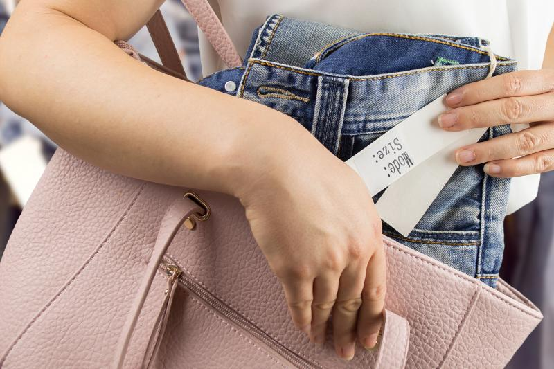 Woman shoplifting a pair of jeans