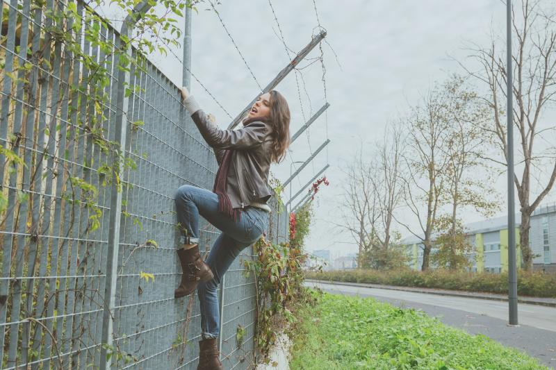 woman climbing on a fence