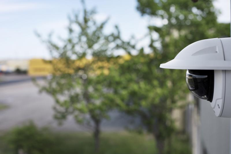 AXIS Q3518-LVE ip camera mounted on a wall in an outdoor environment