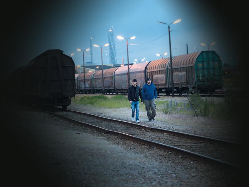 Two men walking on a train track in the dusk