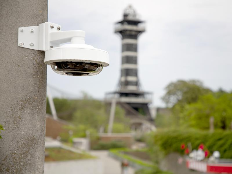 Axis IP camera in daylight at outdoor zoo, mounted to stone wall.