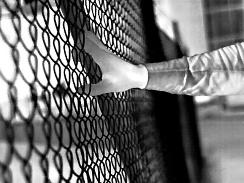 Black and white footage of hand grabbing fence in the dark.