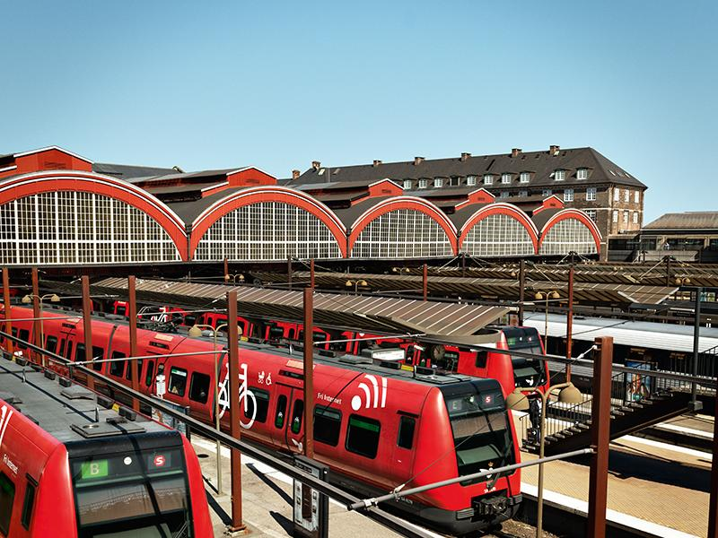 Red trains on station with blue skies