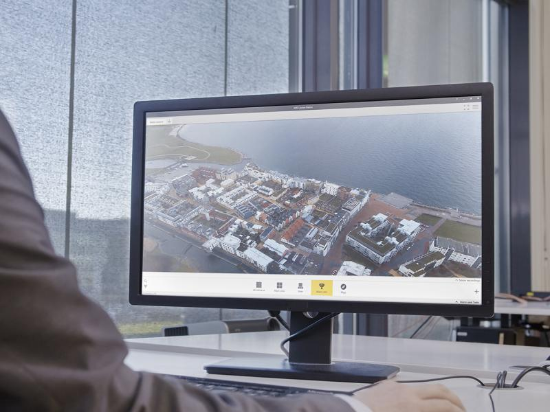 Overview of AXIS Camera Station from a desktop screen, a man sits by the screen