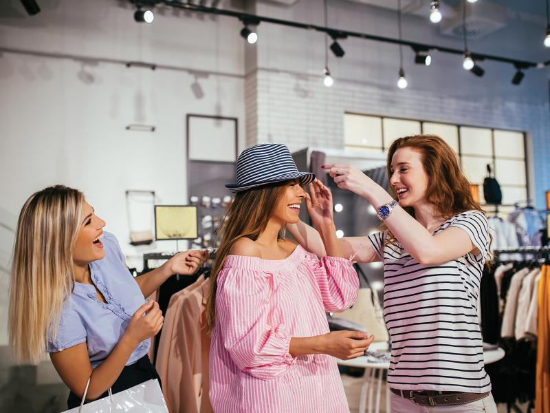 Three women in a boutique, trying on hats and laughing together