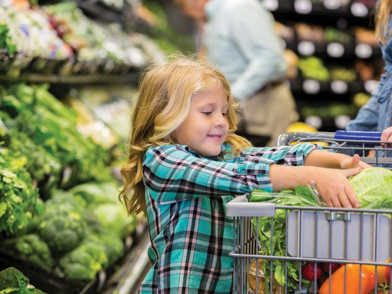 Child picking up vegetables in a grocery store
