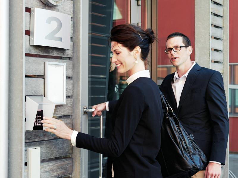 a woman and a man outside a entrance using access control