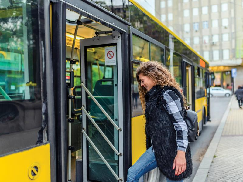 woman boarding a yellow city bus