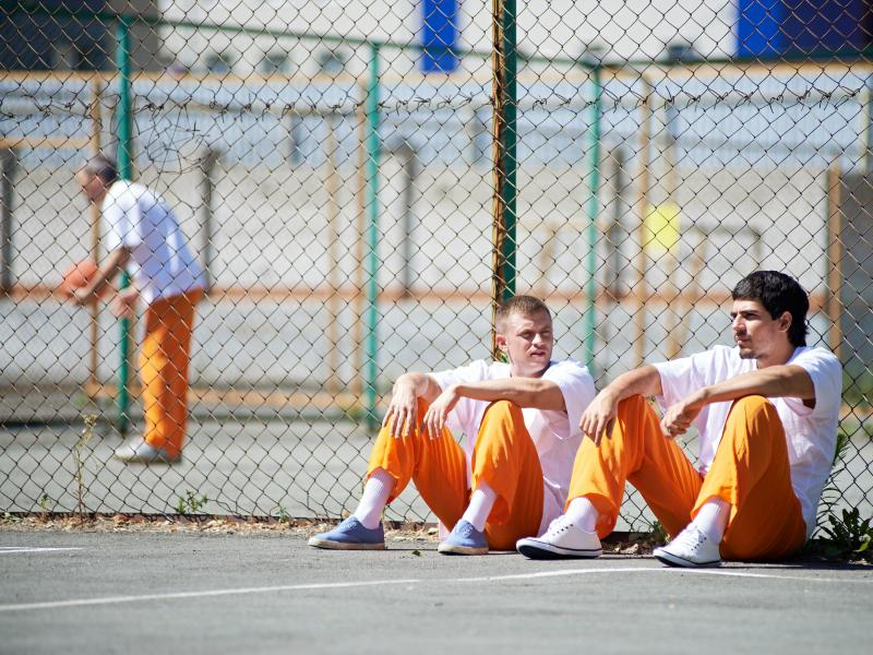 2 prisoners sitting outside along fence