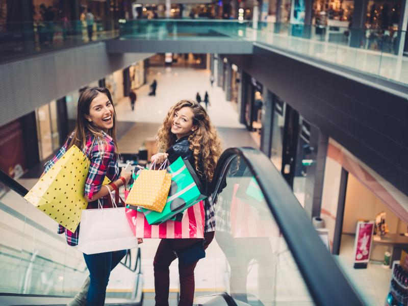 Two women stands in a escalator smiling with several shoppingbags