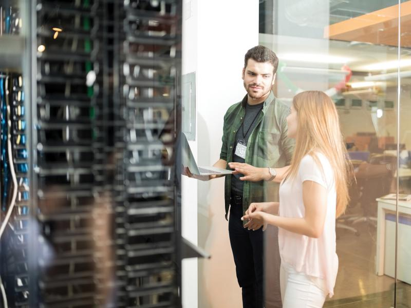 Man and woman talking next to server rack