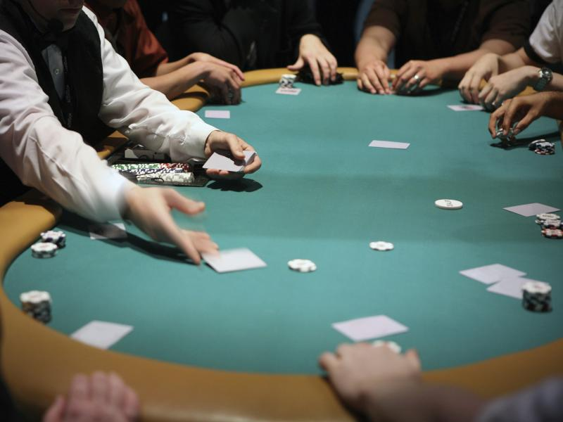 Card dealer hands out cards to poker players
