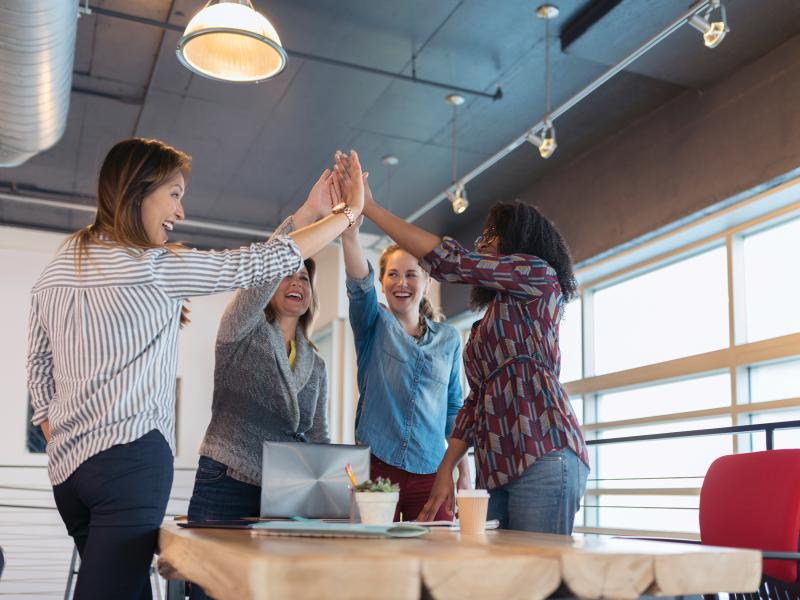 Group-women-high-five-laptop-meeting