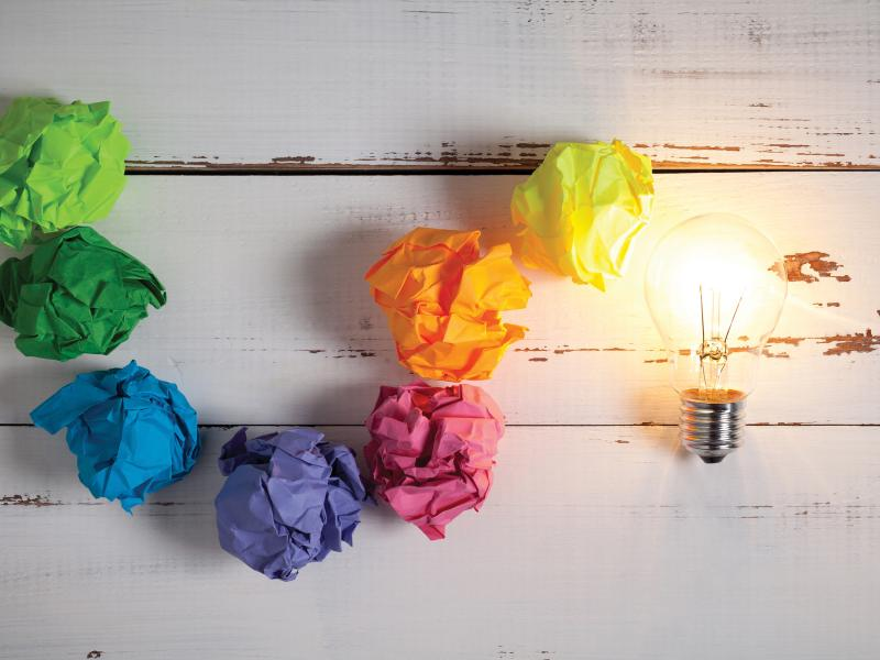 Lightbulb of crumpled paper in rainbow colors.