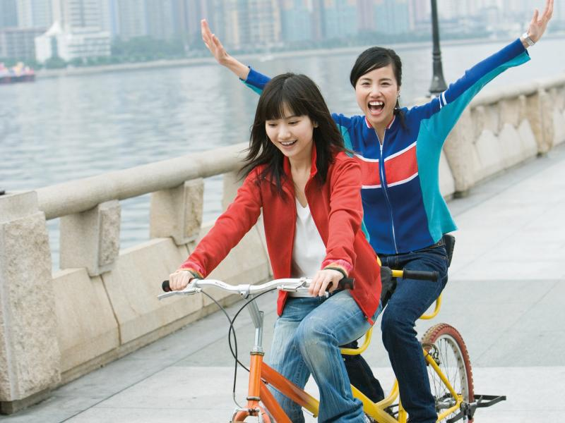 Two young women cycling a tandem bicycle.
