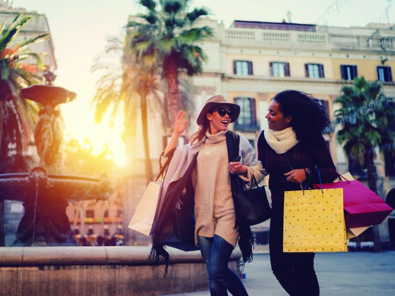two women shopping outdoors, fountain in the background