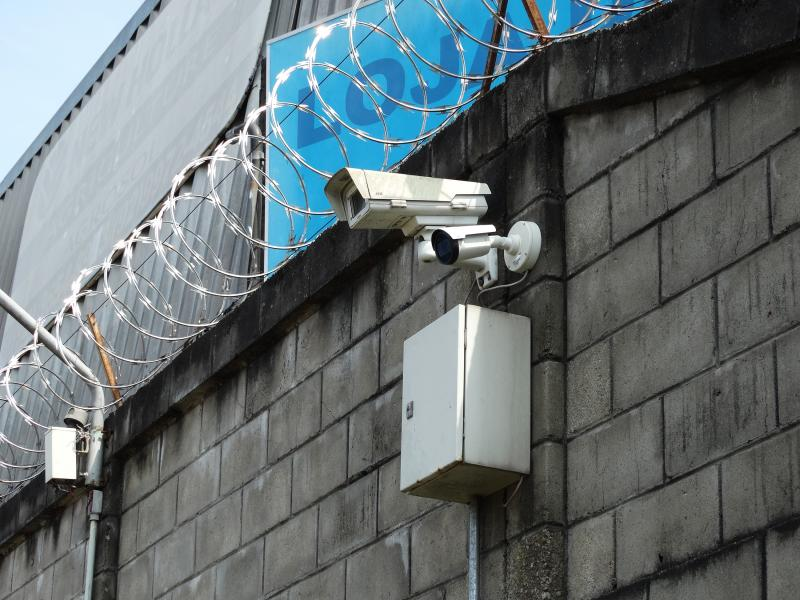 Cameras on brick wall with barbed wire