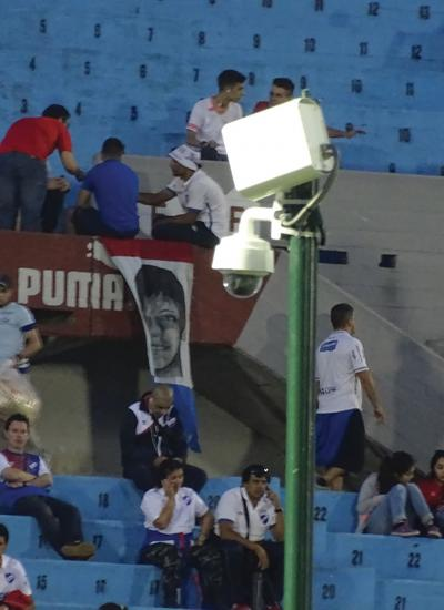 Stadium with blue seats and Axis Camera on a pole.