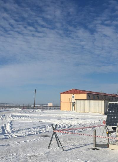 Pole-mounted security camera driven by solar energy in a snowy oil field