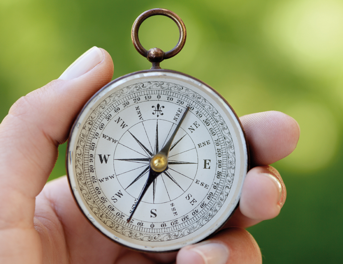 Hand holding compass, green background