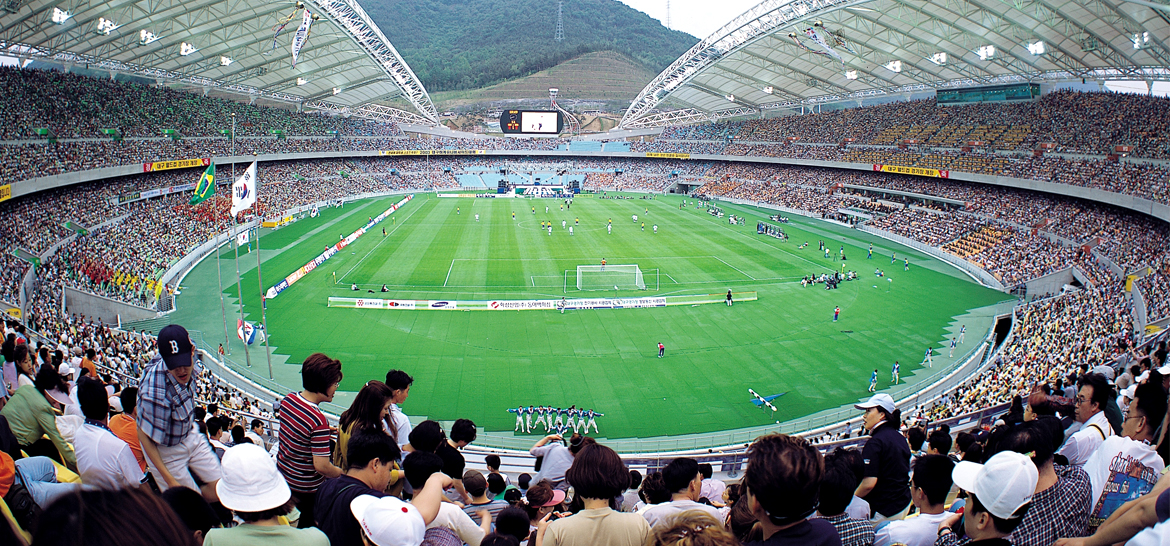 Crowded soccer stadium with mountain surroundings