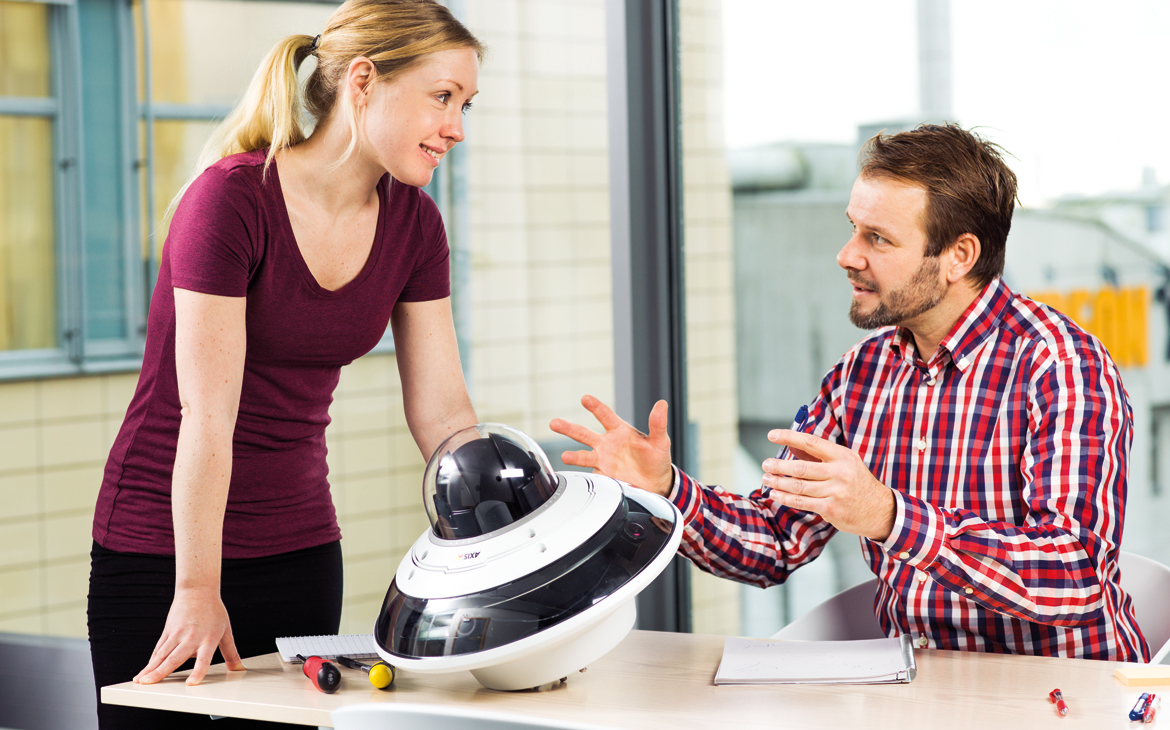 Woman and man discussing the AXIS Q6000-E Network Camera