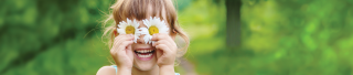 Girl with daisy flowers as eyes smiling